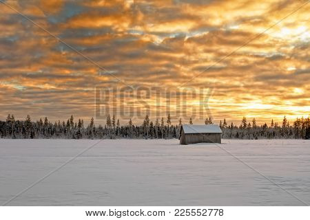 The Cold Winter Sunset Creates Dramatic Colors On The Sky At The Northern Finland. A Small Barn Hous