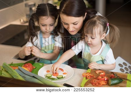 Happy Family Mother And Children Are Preparing Healthy Food, They Make Funny Face With Vegetables Mo