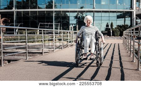 Being Outside. Joyful Nice Disabled Woman Sitting In The Wheelchair And Enjoying Her Walk While Bein