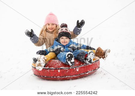 Photo Of Cheerful Girl And Boy Riding Tubing In Winter