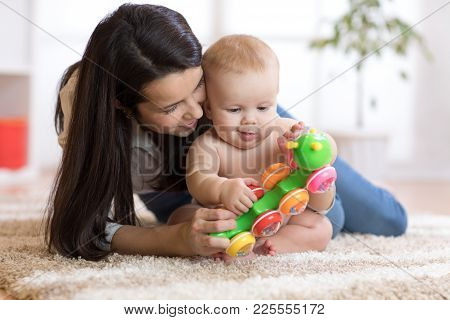 Mother And Her Baby Son Play With Toy In Cosy Children Room