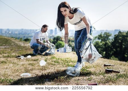 Clean Environment. Nice Pleasant Young Woman Holding A Plastic Bag And Collecting Rubbish While Help