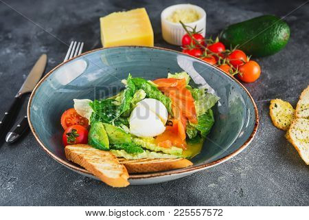 Caesar Salad With Egg, Salmon, Avocado, Cherry Tomatoes And Grilled Toast On Grey Background