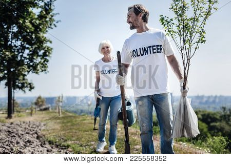 Earth Ecosystem. Joyful Nice Positive Man Holding A Tree And Smiling While Intending To Plant It