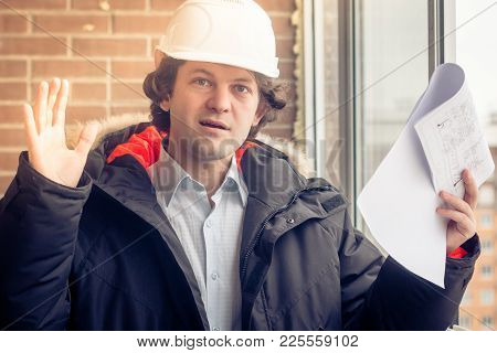 An Angry Disgruntled Builder Worker In A Helmet With Project Drawings Plans In His One Hand And Mobi