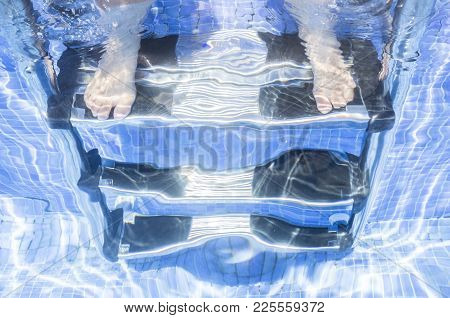Child Girl Sitting On The Swimming Pool Ladder With Legs Underwater. Children Summer Concept