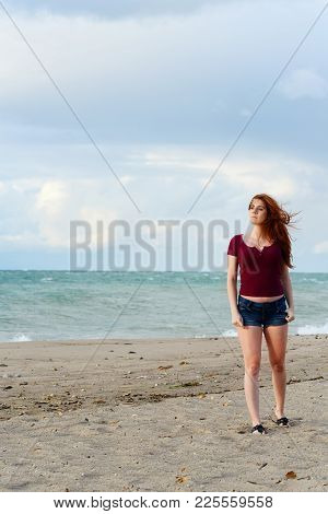Redhead Woman On Beach With Hair Blowing In Wind