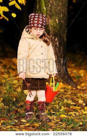 Cute toddler girl walks in autumn forest