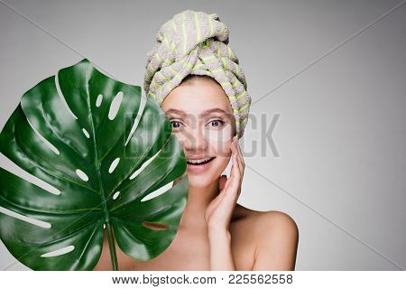 A Happy Woman With A Towel On Her Head Applied Patches Under Her Eyes And Covered Herself With A She