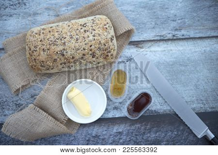 A Seeded Bread Roll With Butter, Jam And A Bread Knife On A Wooden Background