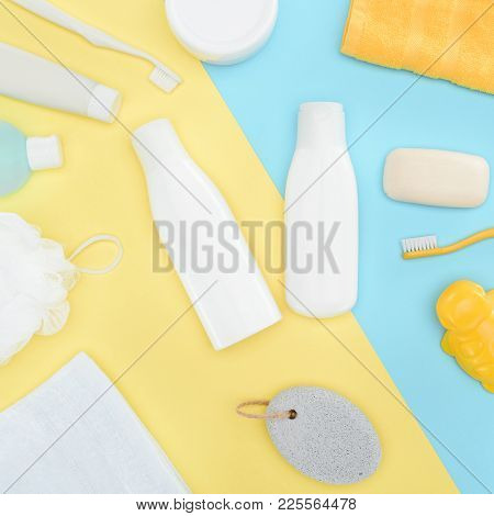Flat Lay With Body Lotion In Bottles, Toothbrushes, Pumice, Towel And Soap, Isolated On Blue And Yel