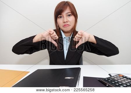 Unhappy Business Woman With Thumb Down In Office - Calculator, File And Document On Desk.