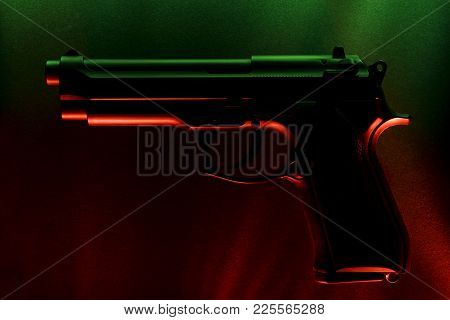Firearms. Against The Background Of Blue And Red Shades Of Material. Light Effect. Close-up.