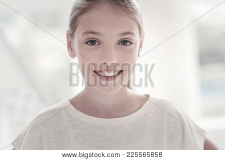 Good Mood. Pretty Happy Vigorous Long-haired Grey-eyed Girl Smiling And Wearing A White- T-shirt And
