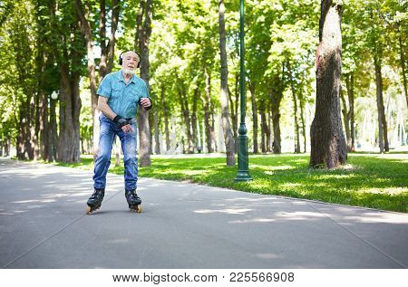 Active Old Age. Happy Senior Man Roller Skating Outdoors. Elderly Man Enjoying Sports In Sunny Summe
