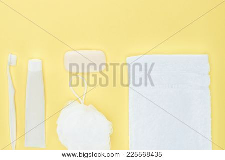 Top View Of White Toothbrush, Toothpaste, Towel, Washcloth And Soap, Isolated On Yellow