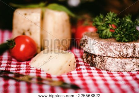 Close Up Rustic Cheesehead With Herbs, Rye Bread And Tomatoes On Checkered Tablecloth, Selective Foc