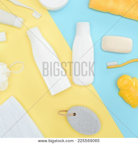 Top View Of Body Lotion In Bottles, Toothbrushes, Pumice, Towel And Soap, Isolated On Blue And Yello