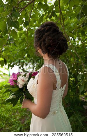 Beautiful Bride In Wedding Dress With Bouquet Of Peonies At The Park