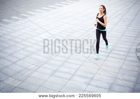 Young Sporty Woman Running Outdoors. Fit Girl In Sports Wear Jogging In The City, Copy Space. Active
