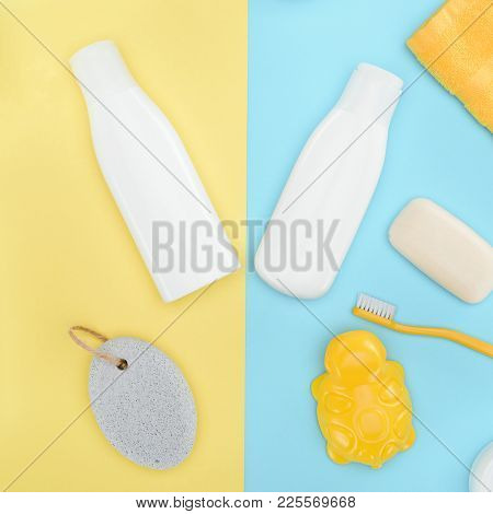 Flat Lay With Bottles Of Lotion, Toothbrush, Pumice, Soap And Bath Toy, Isolated On Blue And Yellow