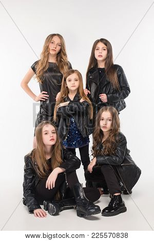 Studio Portrait Of Five Young Attractive Fashion Caucasian Teen Girls Dressed In Black Leather Jacke