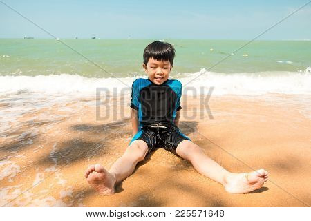 A Boy In Swimming Suit Is Sitting On The Beach And Playing Sand At The Sea In The Sunny Day In Summe