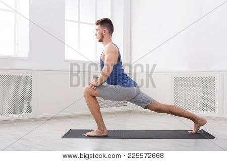 Man Warmup Stretching Training At White Background Indoors, Copy Space. Young Boy Makes Exercise, Si