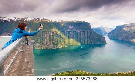 Tourism Vacation And Travel. Woman Tourist Taking Photo With Camera, Enjoying Aurland Fjord View Fro