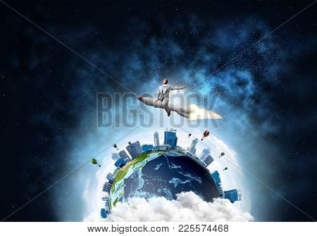 Conceptual Image Of Young Businessman In Suit Flying On Rocket With Planet Earth And Open Space On B