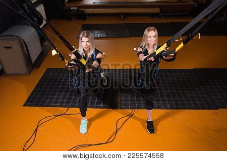 Two Beautiful Woman In Electrical Muscular Stimulation Suit Doing Squat Exercise For Back And With S