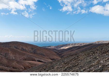 Arid Rolling Landscape With Ocean In Background Under Blue Sky On Fuerteventura Island