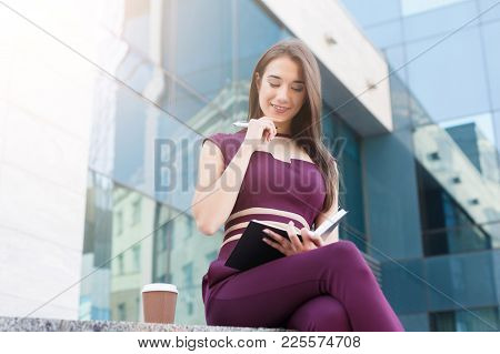 Confident Successful Businesswoman Taking Break At Lunch Time, Holding Take Away Coffee And Reading