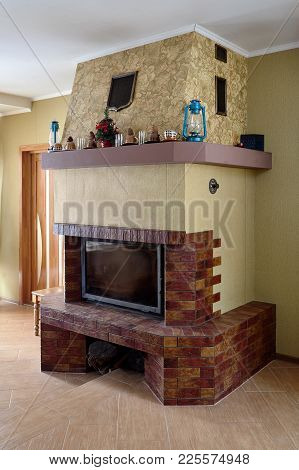 Fireplace In Livingroom With Cups, Lamps And Christmas Tree On Mantelpiece