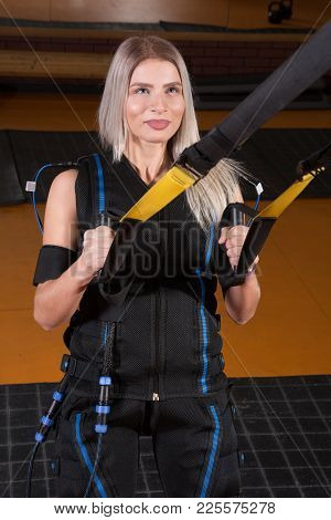 Beautiful Woman In Electrical Muscular Stimulation Suit Doing Squat Exercise For Back And With Suspe