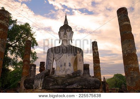 Ancient Sculpture Of The Sitting Buddha Close Up At Sunset. Historical Park Of The Sukhothai City, T