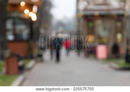 Blurred Abstract Background. Unrecognizable Silhouettes Of People Walking On City Street