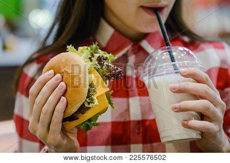 Woman Eat Humburger And Drink Milk Shake Close Up