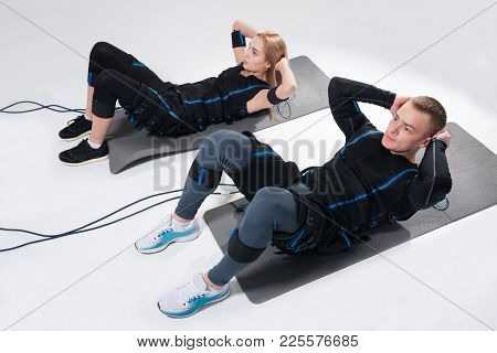 Young Man And A Woman In An Electric Muscular Suit Are Trained To Stimulate Themselves. Fitness In E