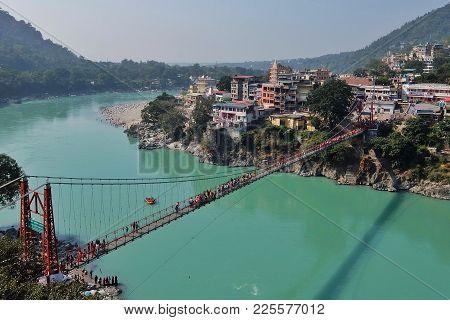 Rishikesh, India - November, 5th, 2017. View Of Ganga River Embankment And Lakshman Jhula Bridge In