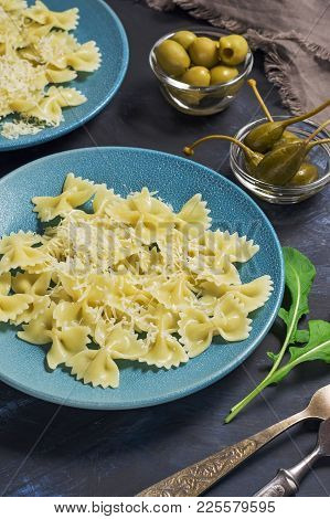 Pasta Are On A Blue Plate With Olives And Capers On A Dark Background