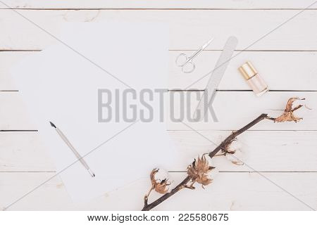 Top View Of Scissors, Nail File And Nail Polish With White Paper On Wooden Table
