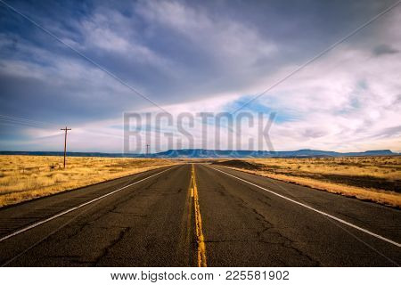 A Highway Cutting Between Golden Pasture Land With Mountains In The Distance Under A Cloudy Sky In A