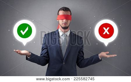 Blindfolded businessman with checked and x mark above his hand