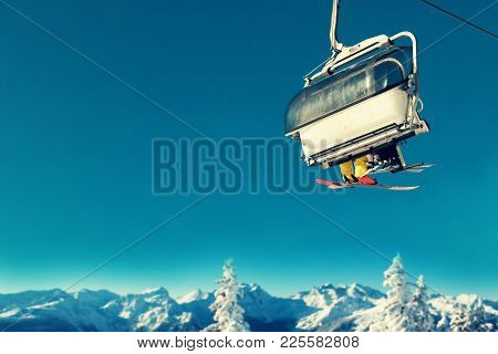 People In Chairlift At Ski Resort Above Snowy Trees And Mountains