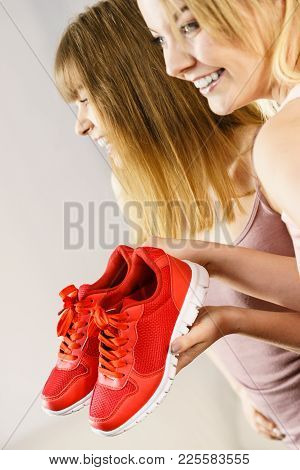 Two Happy Sporty Smiling Women Presenting Sportswear Trainers Red Shoes, Comfortable Footwear Perfec