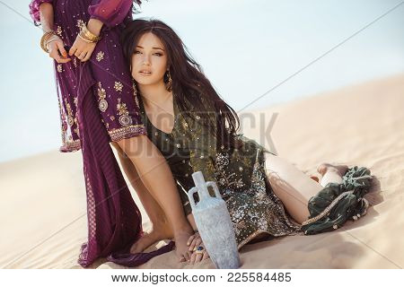 Women Traveling In Desert. Dehydration, Overheating, Thirst And Heat Stroke Concept Image With Two S