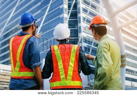 Back View Group Of Engineer, Technician And Architect With Safety Helmet Planning About Building Pla