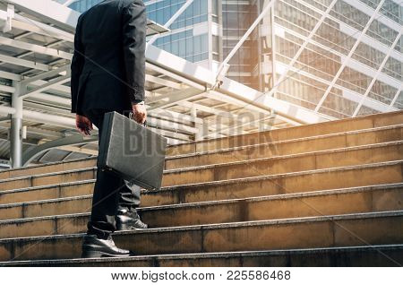 Young Handsome Business Man Holding Briefcase And Walking Up The Stairs Going To Work Time At Mornin