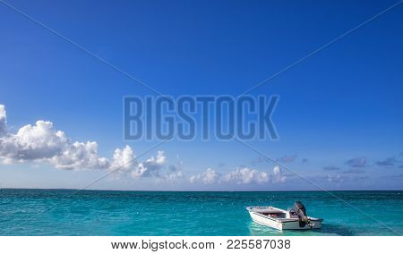 A Small Motorized Rescue Boat Docked By An Expansive Ocean View Under Blue Cloudy Sky
